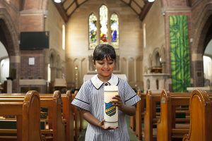 McAuley Catholic Primary School Rose Bay student carrying candle at church
